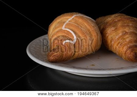 Cinnamon crescents croissant on white plate on the black background