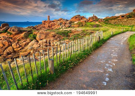 Amazing sunset with lighthouse of Ploumanach Mean Ruz in Perros-Guirec on Pink Granite Coast and spectacular walkway near ocean Brittany France Europe