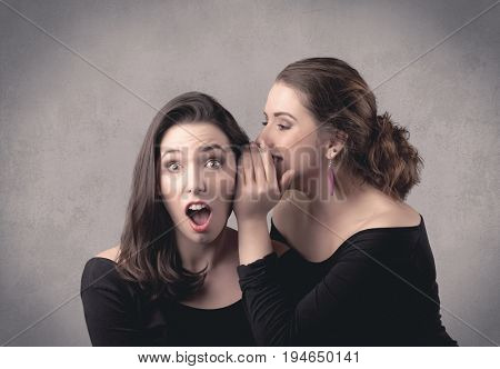 Two fancy dressed actress girls with long hair and make up whispering in front of grey urban background concept.