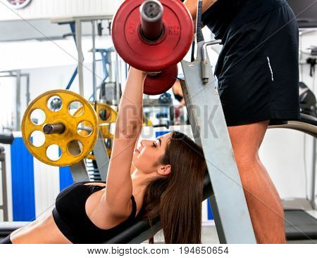 Fitness friends workout gym. Woman working on bench press. She lifting barbell. Trainer backs girl while taking exercises. Group work people on treadmill background. Shooting from bottom point.