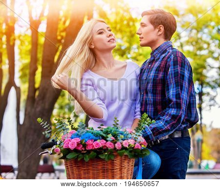 Walking bike of couple in park and kissing. Summer friends walk outdoor. First date of two young people in good weather day. Sun backlight on background. Love at first sight.