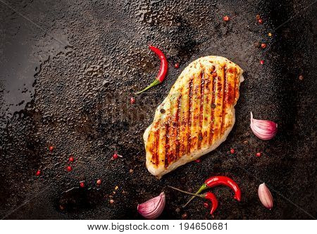 Spicy grilled chicken breast with chilli and garlic on a roasting tin.