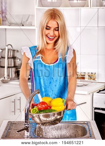 Fruit and vegetable wash of woman on kitchen home. Girl washing fruit under pouring water tap in colander sink indoor. Vegetables from your own kitchen garden.