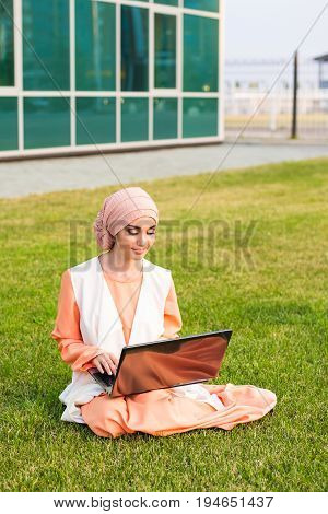 Successful Arab woman and laptop. Arab businesswoman wearing hijab working on a laptop in the park