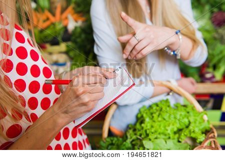 Young woman checking purchases list. Girl with a notebook in hands. Shopping list in hand.