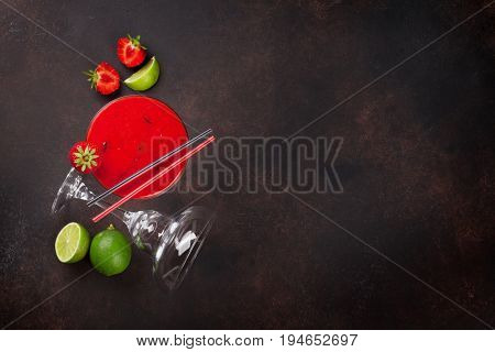 Strawberry margarita cocktail on dark stone table. Top view with copy space