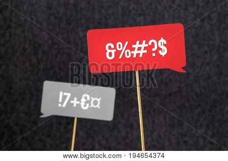 Argument, fight, curse or swearing concept. Disagreement on an online forum. Two red and gray speech bubbles argue. Speech balloon cut from paper of cardboard with wooden stick on a dark background.