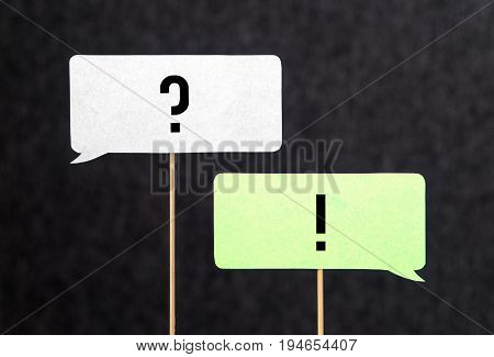 Question and answer. Interview, education and communication concept. Question and exclamation mark on cardboard speech bubble or balloon on wooden stick.