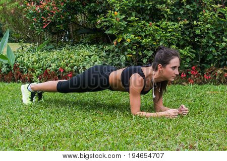 Pretty young sportswoman doing plank exercise on grass in city park.