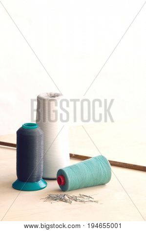 Spools of thead and pins on table