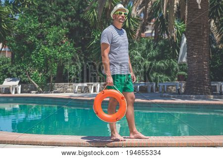 Portrait of yong tourist holding lifebuoy at the poolside