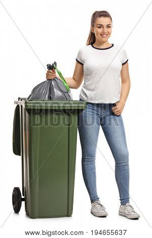 Full length portrait of a young girl throwing out the garbage isolated on white background