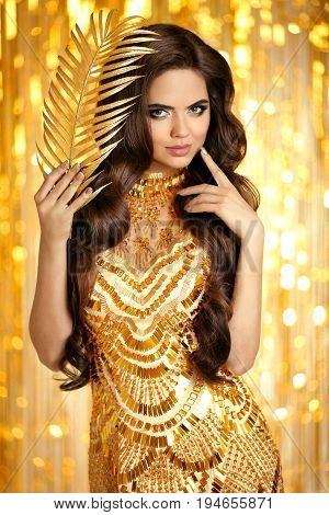 Elegant Brunette In Golden Sparkling Dress. Fashion Glamour Style. Beauty Makeup And Wavy Hairstyle.
