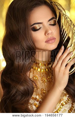 Golden Makeup. Elegant Brunette Woman. Fashion Jewelry. Wavy Hair Style. Matte Lips. Sexy Lady Model