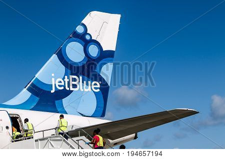 Grenada June 22 2017: Members of service crew are entering a JetBlue airplane following its landing at Maurice Bishop airport.