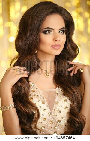 Beauty Fashion Woman In Gold. Elegant Brunette With Makeup, Long Wavy Hair Style, Pendant Golden Jew