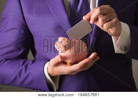 hands putting blank business card in piggy bank for saving on grey background. Stylish formal blue suit and tie. Banking money loan moneybox ecash and information