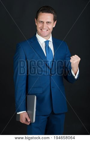 Businessman with celebrating gesture and laptop. Happy man or manager smiling in blue formal suit on dark background. Technology for business. Success and victory