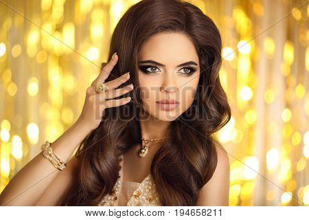 Beautiful Fashion Woman In Gold. Elegant Brunette With Makeup, Long Wavy Hair Style, Pendant Golden