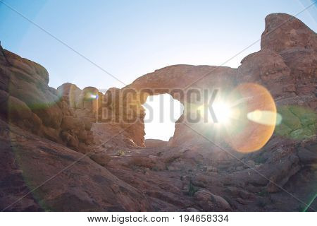 USA, sun shining through rock formation in desert