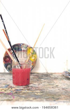 Closeup of glass with paintbrushes in artist's studio