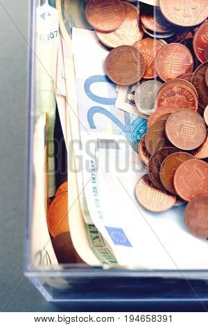 Plastic moneybox with Coins and paper Euro currency, view from above