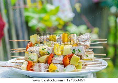 Tasty skewers of fresh fish with vegetables and apples on a wooden shish kebab, cooked on a grill