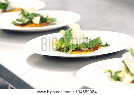 Closeup of four plates of salads with grated cheese