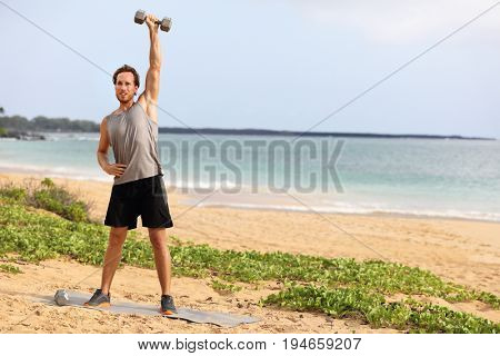 Fitness man doing weight lifting dumbbell overhead raise exercise - shoulder press or single front raise dumbbell snatching. Athlete exercising at outdoor gym on beach.
