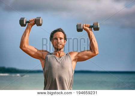 Fitness weightlifting man doing shoulder press. Gym workout lifting dumbbell weights. Male athlete with muscular arms with dumbbells overhead training biceps.