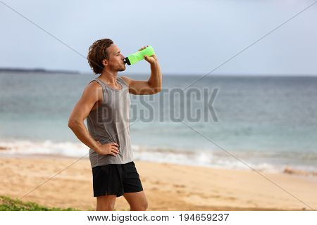 Fitness runner man drinking water bottle during summer heat at beach run race. Running athlete thirsty during exercise outdoors. Wellness healthy active lifestyle.
