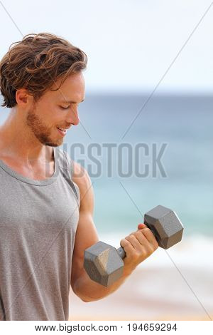 Fitness gym workout man lifting dumbbell weight doing bicep curl training arm exercise for biceps muscles.