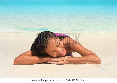 Beach summer relaxation spa retreat woman sunbathing lying down on white sand in tropical paradise. Bikini Asian girl relaxing sleeping enjoying sun getaway.