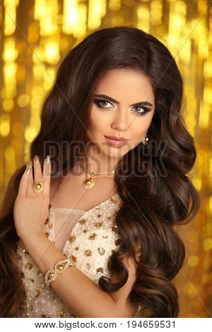 Elegant Brunette Woman. Fashion Jewelry. Wavy Hair Style. Matte Lips Makeup. Sexy Girl Model In Gold