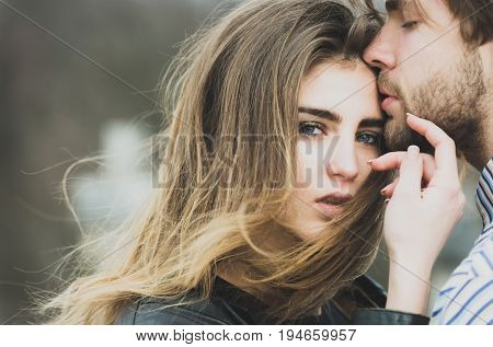 Sexy man and girl with fashion makeup and long hair touching each other with love and tenderness. Young couple of heterosexual lovers outdoors