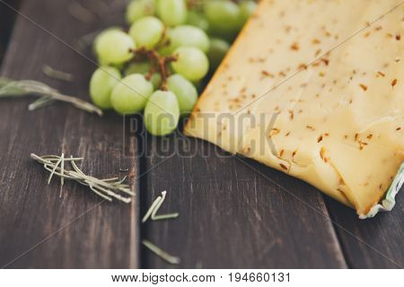 Gouda pesto cheese closeup. Still life with white grapes and rosemary on rustic wood background, copy space