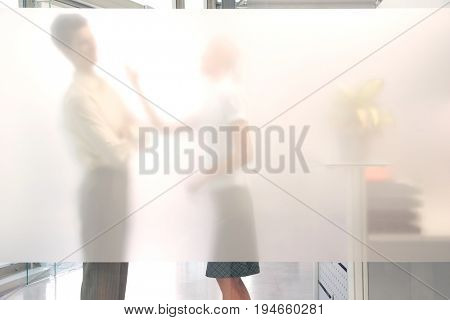 Side view of a female office worker arguing with male colleague behind translucent wall in office