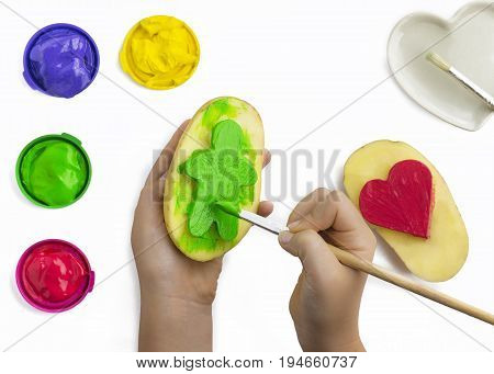 Childs hand play painting with potato stamps brushing green on a figure shape red yellow and purple poster paints some isolated objects on a white background copy space