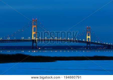Mackinac Bridge, at night, as its lights twinkle and create reflections on winter ice.