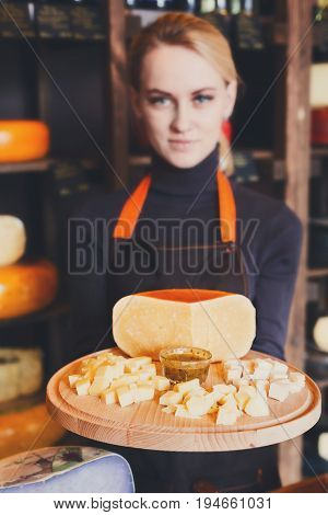 Parmesan cheese platter. Female shop assistant suggesting diced parmesan with sauce on wooden plate, grocery shop background