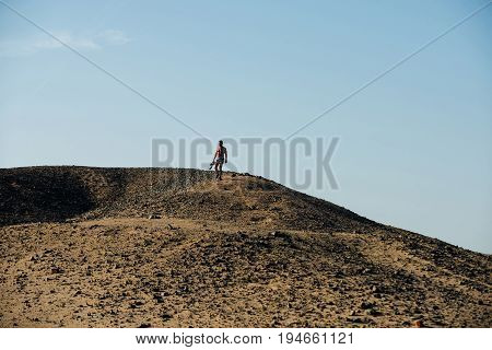 Photographer with camera climbing down desert hill with rocky sand surface on sunny day on blue sky. Arid landscape. Hobby. Active leisure. Travel travelling and hiking. Summer vacation. Wanderlust