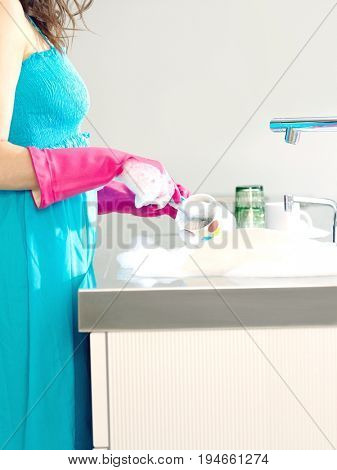 Side view midsection of a woman in blue dress and rubber gloves washing dishes