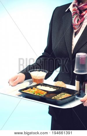 Midsection of stewardess holding tray with airplane food on blue background