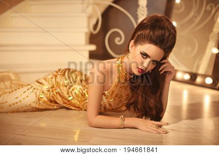 Elegant Brunette Sexy Woman In Fashionable Golden Dress Lying On The Floor In Luxury Interior. Attra