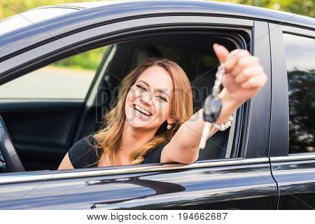 Young woman getting her key in the car. Concept of rent car or buying car.