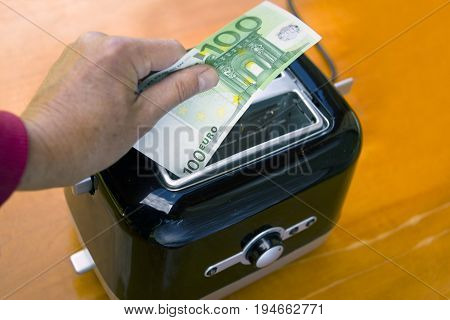 Hand roasting a hundred euro banknote in toaster concept of life expenses