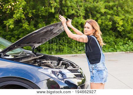 Broken car, accident, feeling confusion and people concept. Portrait of embarrassed young woman with broken car