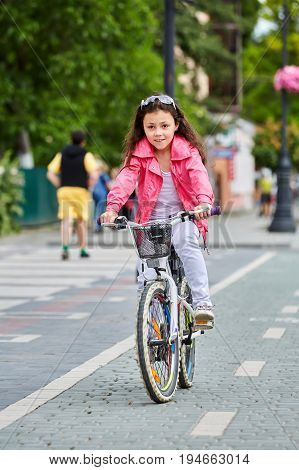 Cute kid girl with long hair in red jacket rides her white bike an city park.