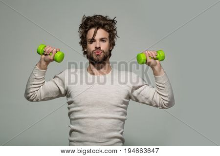 morning exercise of man with barbell or dumbbell workout has disheveled and uncombed long hair and beard on face in white underwear on grey background morning exercise and wake up barbershop sport