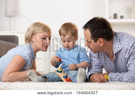 Nuclear family with one year old baby boy playing together on living room floor.